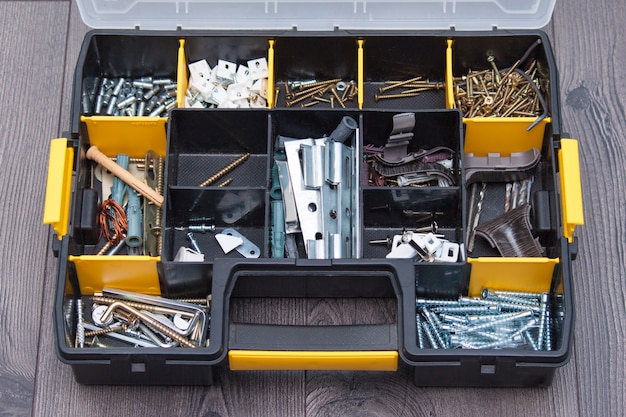 Custodia in plastica con elementi hardware, primo piano. scatola con chiodi, viti, bulloni, tasselli.