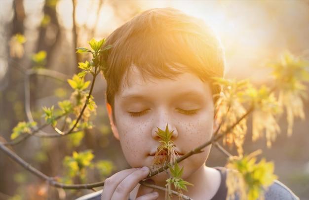 Cute baby con le lentiggini sul viso respira aria fresca di primavera.