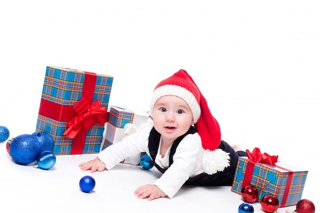 Cute baby in un cappello rosso di capodanno con un sorriso sul suo volto