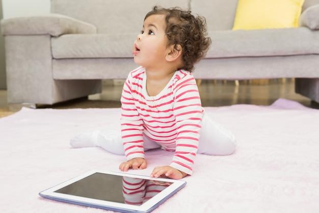 Cute baby sul tappeto con tablet a casa
