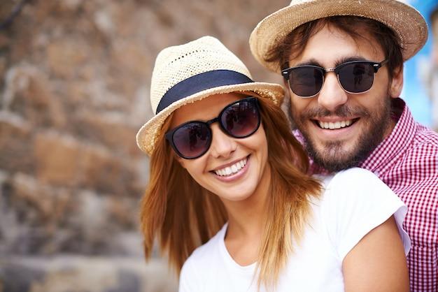 Cute coppia con cappelli e occhiali da sole close-up