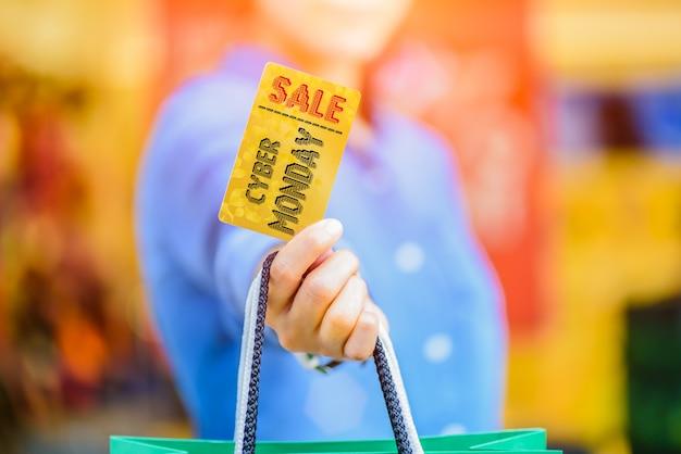 Cyber monday sale concept. donna che tiene i sacchetti della spesa e carta di credito