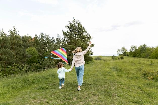 Da dietro negozio mamma e bambino giocano con l'aquilone