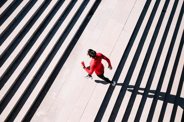 Da sopra lo sportivo che corre sulle scale