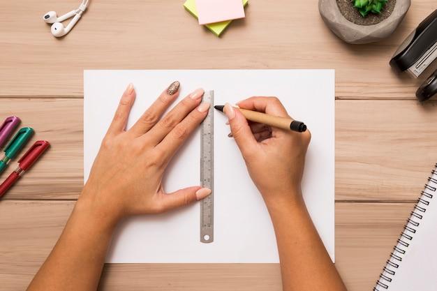 Da sopra mani femminili che attingono foglio di carta con penna e righello