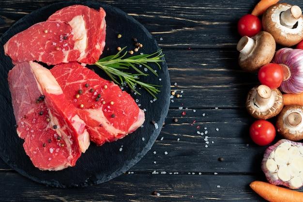 Da un lato del tavolo ci sono le verdure dall'altro lato di una bella carne di manzo succosa e cruda. scegli il tuo cibo.