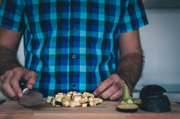Dadi di melanzane sul tagliere con un uomo in camicia a scacchi blu