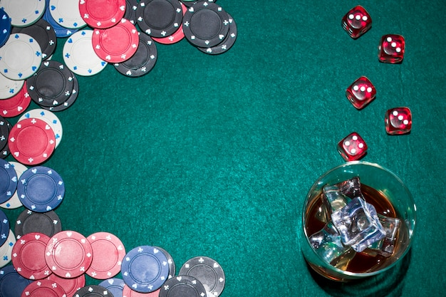 Dadi rossi; fiches del casinò e bicchiere di whisky con cubetti di ghiaccio sul tavolo da poker verde