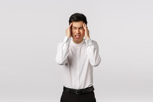 Dai, devi pensare. giovane asiatico in tensione e angoscia che soffre di forti mal di testa, occhi chiusi, accigliato e smorfie di dolore, sfregamento delle tempie, mal di testa, bisogno di antidolorifici,