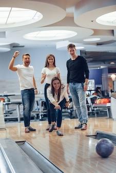 Dai, fai uno sciopero. i giovani amici allegri si divertono al bowling durante i fine settimana