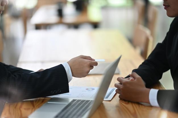 Dai il biglietto da visita in bianco al colpo del primo piano dell'ospite con la conversazione di affari.