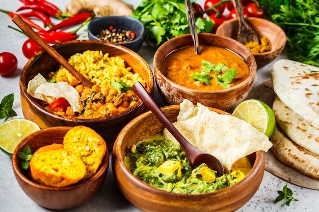 Dal, palak paneer, curry, riso, focaccia, chutney in ciotole di legno sul tavolo bianco.