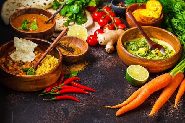 Dal, palak paneer, curry, riso, focaccia, chutney in ciotole di legno sul tavolo scuro.