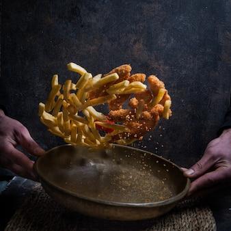 Dall'alto crocchette di pollo con patatine fritte e mano umana in volo