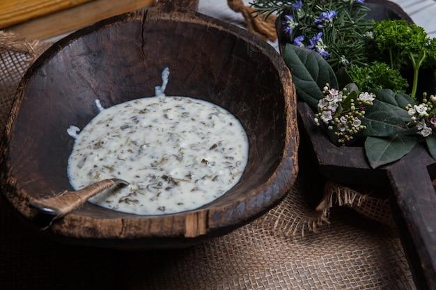 Dall'alto dovga con foglie di rosmarino e cucchiaio in un piatto di legno