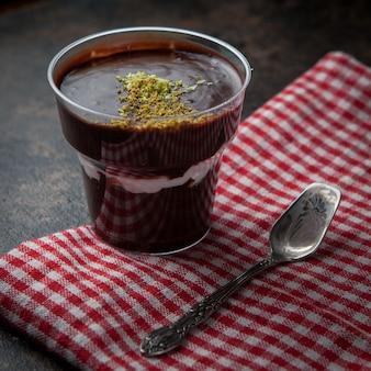 Dall'alto frullato al cioccolato con briciole di noci e cucchiaio e straccio antichi in bicchiere di plastica