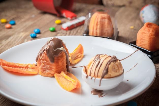 Dall'alto gelato con sciroppo di cioccolato e albicocche secche in un piatto bianco rotondo