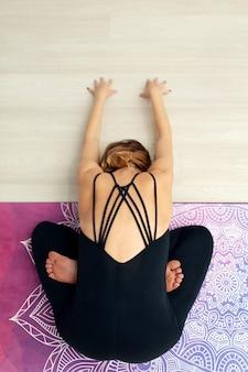 Dall'alto giovane donna praticare yoga che si estende in palestra