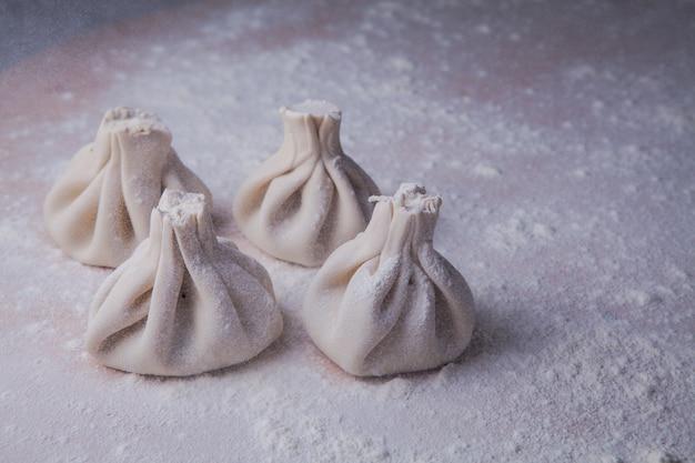 Dall'alto khinkali con farina nel tagliere di pasta