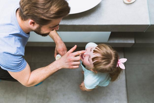 Dall'alto padre spalmando la crema sul naso della figlia