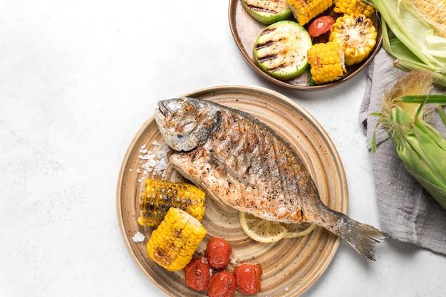 Dall'alto pesce alla griglia con limone servito con verdure diverse sui piatti