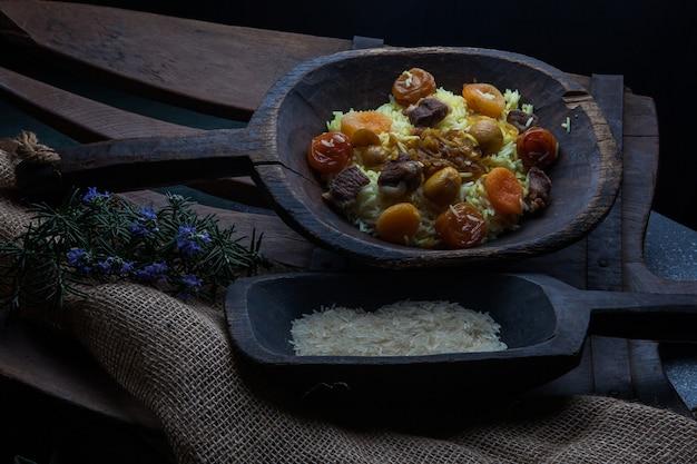 Dall'alto pilaf con raduno e frutta secca e castagne e riso e foglie di rosmarino in un piatto di legno