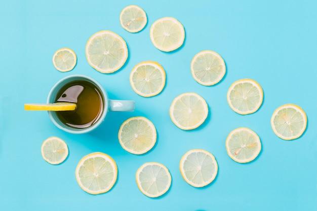 Dall'alto tazza di tè al limone con un motivo di agrumi su sfondo blu
