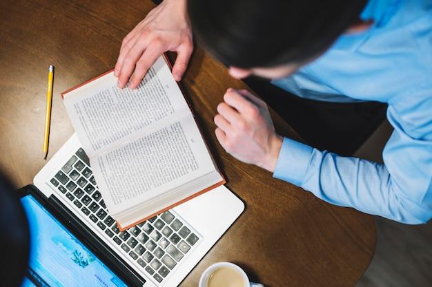 Dall'alto uomo che studia con il libro e il portatile
