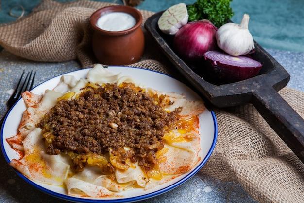 Dall'alto xengel con yogurt e cipolla e aglio e forchetta nel piatto rotondo
