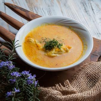 Dall'alto zuppa di pollo con foglie di rosmarino e verdure in tavola