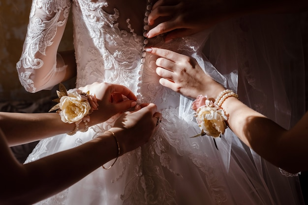 Damigella d'onore aiutando la sposa fissare corsetto e ottenere il suo vestito, preparando la sposa in mattinata per il giorno del matrimonio.