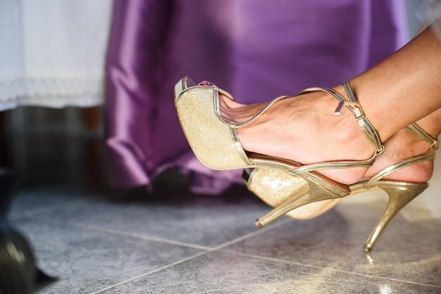 Damigella d'onore che aiuta la giovane sposa a indossare le scarpe prima della cerimonia.