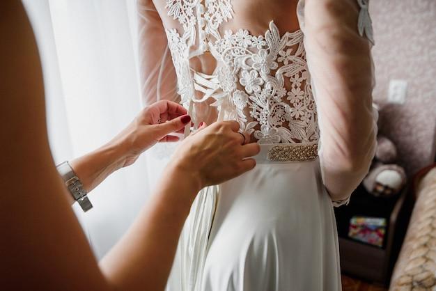 Damigella d'onore che lega i nastri sul vestito bianco da sposa