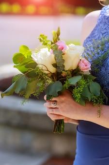 Damigella d'onore detiene il bouquet di eleganza con foglie e rose