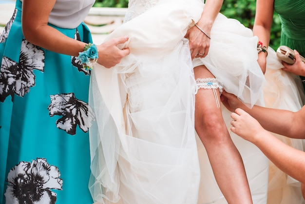 Damigelle d'onore che aiutano la giovane sposa a indossare la giarrettiera sulla gamba