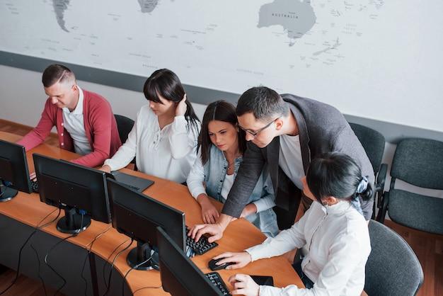 Dammi il tuo computer per un secondo. uomini d'affari e manager che lavorano al loro nuovo progetto in classe