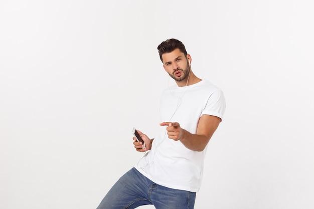 Dancing bello casuale dell'uomo con il telefono cellulare isolato su bianco