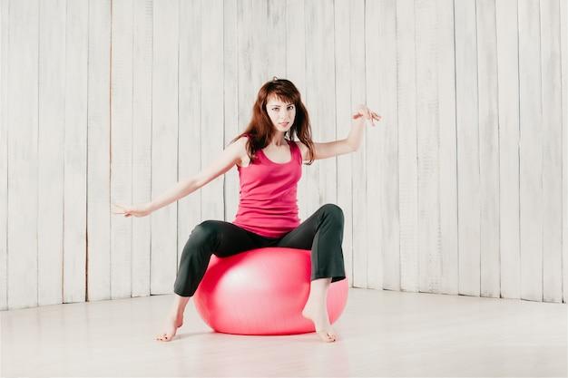 Dancing grazioso della ragazza su un fitball rosa, mosso, alta chiave