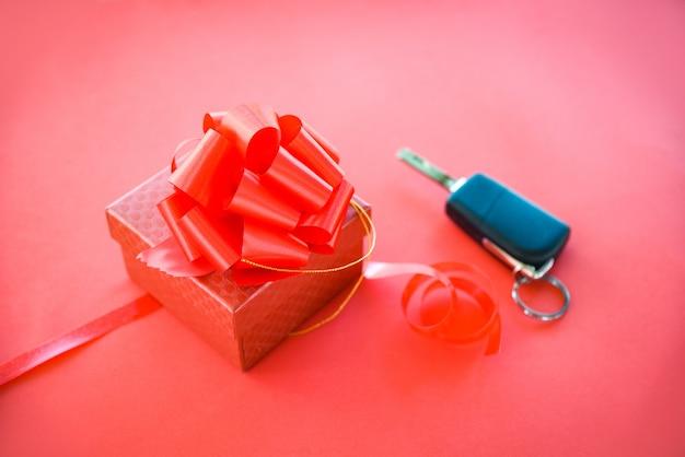 Dare il concetto chiave di auto regalo confezione regalo rosso con fiocco di nastro rosso e auto chiave come presente su sfondo rosso