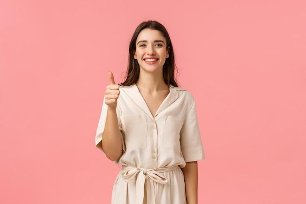Dare un feedback positivo, raccomandazione. bella ragazza allegra e tenera in splendido abito, mostrando il pollice in su in segno di approvazione, gesto soddisfatto o pubblicitario, sorridente come un prodotto, muro rosa