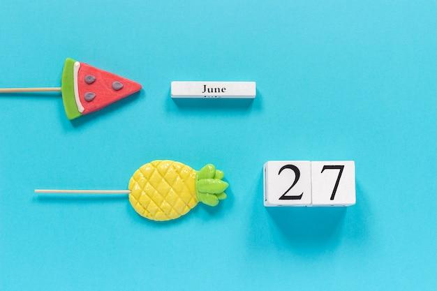 Data del calendario 27 giugno e frutta estiva caramelle ananas, lecca lecca cocomero.