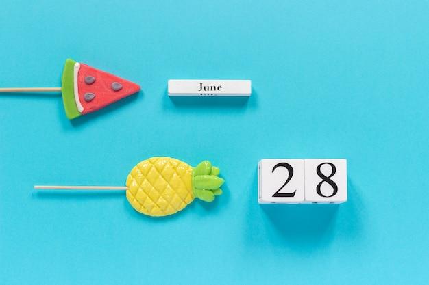 Data del calendario 28 giugno e frutta estiva caramelle ananas, lecca lecca cocomero