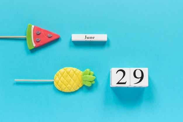 Data del calendario 29 giugno e frutta estiva caramelle ananas, lecca lecca cocomero.