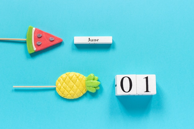 Data di calendario 1 giugno e frutta estiva ananas caramelle, lecca-lecca cocomero sul bastone.