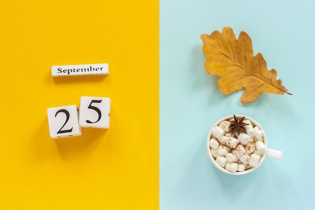 Data di calendario, tazza di cacao con marshmallow e foglia gialla d'autunno