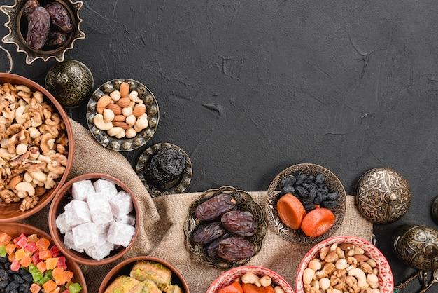 Date deliziose; noccioline; frutta secca e lukum dolce sulla ciotola metallica e di terra su sfondo nero