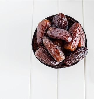 Date organiche isolate medjul in ciotola della noce di cocco su fondo bianco.