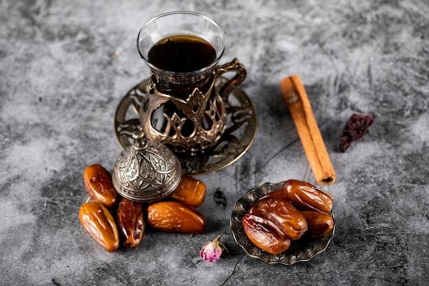 Date orientali in un piattino in stile etnico con un bicchiere di tè e bastoncini di cannella