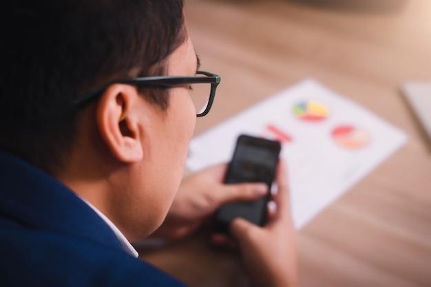 Dati di serching dell'uomo d'affari con lo smartphone fra la riunione del brainstorming di successo corporativo