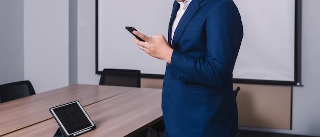 Dati serching dell'uomo d'affari con lo smartphone fra la riunione del brainstorming corporativo di successo